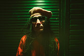 istock Portrait of man with dreadlocks lit by neon colored lights at night 1177259997