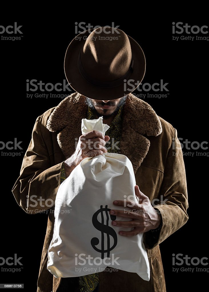 Portrait Of Man With Fedora Hat Holding Money Bag stock photo