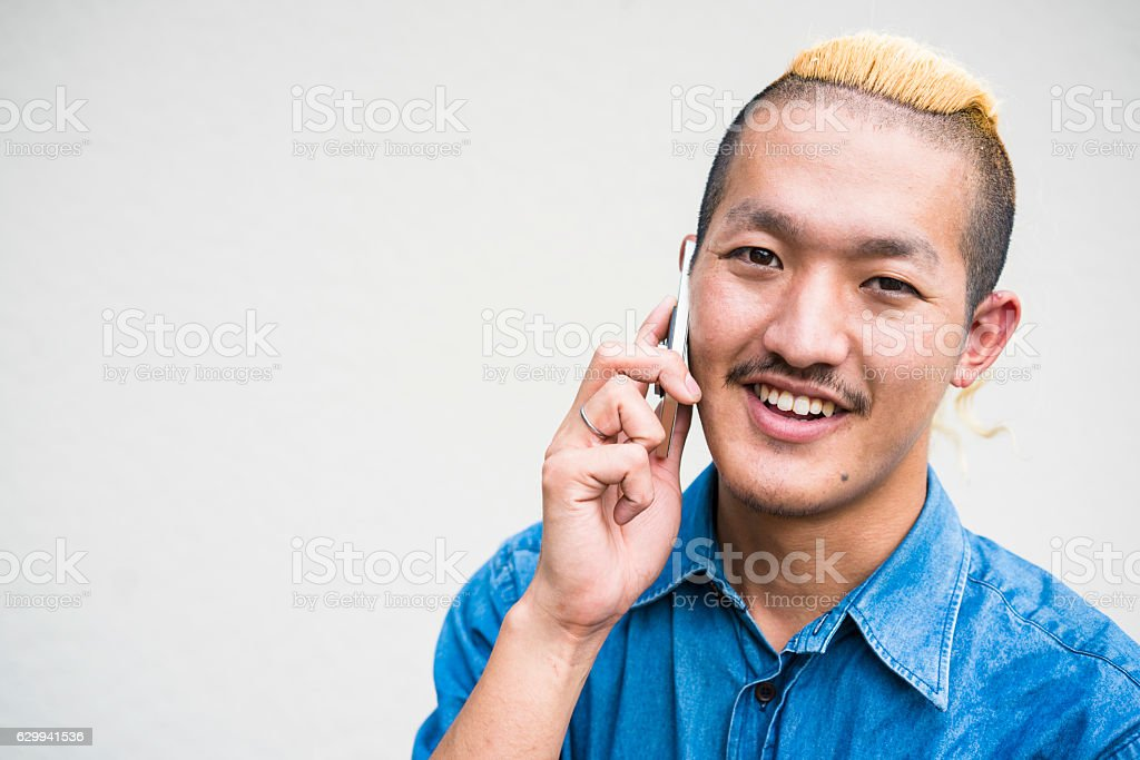 Portrait of man with Iroquois hair style and mobile stock photo