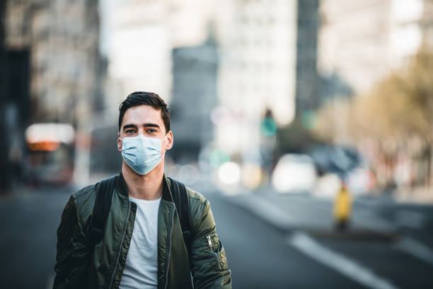 Portrait Of Man With Mask On The Street. Concept, diseases, viruses, allergies, air pollution. Portrait of young man wearing a protective mask, walking in the city.The image face of a young man wearing a mask to prevent germs, toxic fumes, and dust. Prevention of bacterial infection Corona virus or Covid 19 in the air around the streets and gardens. pollution mask stock pictures, royalty-free photos & images