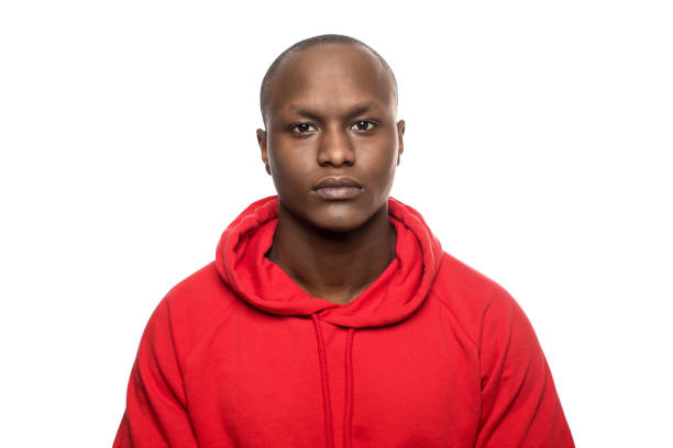 Portrait of man with shaved head in red casuals Portrait of young man with shaved head. Serious male is against white background. He is wearing red casuals. only young men stock pictures, royalty-free photos & images