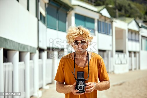Portrait of smiling mid adult man with vintage camera. Male hipster is standing against beach huts. He is enjoying summer at beach.
