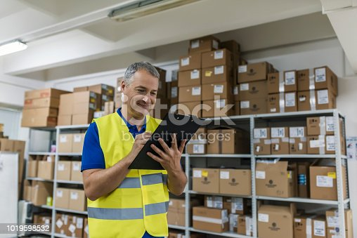 Wholesale, logistic, people and export concept - businessman or supervisor with clipboards at warehouse