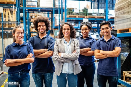 Portrait of successful logistics team standing together. Female manager with warehouse workers.