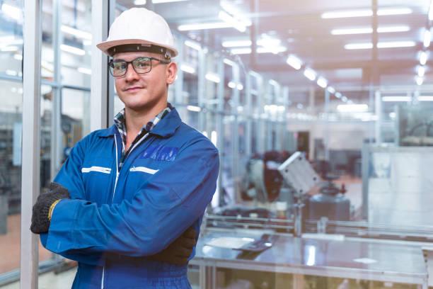 retrato de hombre manual trabajador está de pie con confianza con vestido de suite de trabajo azul y casco de seguridad en frente de la pared de vidrio de la fábrica de la industria limpia de alta tecnología. concepto de trabajador de la industria intel - ingeniero fotografías e imágenes de stock