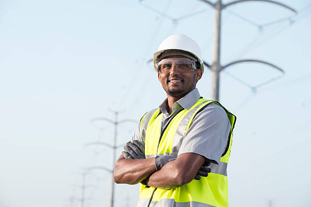 Portrait of manual worker / electrician / lineman / engineer / technician. Portrait of manual worker in Personal protective equipment (PPE) standing under high voltage transmission lines against tubular transmission towers. power occupation stock pictures, royalty-free photos & images