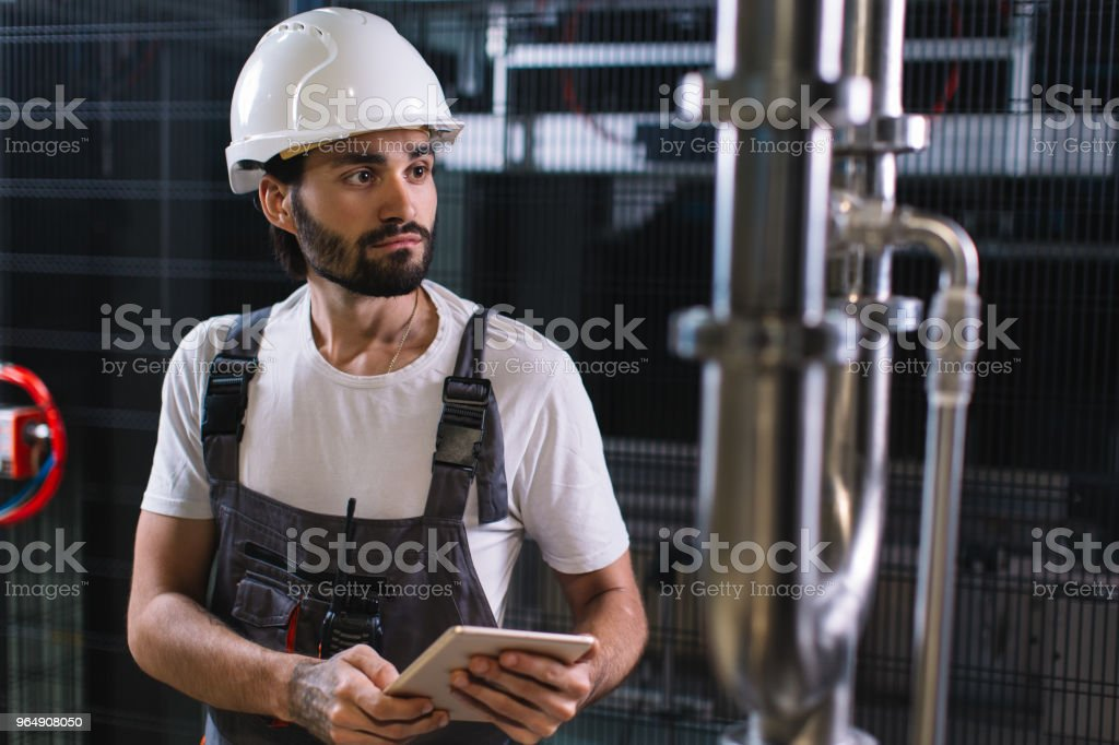 Portrait of manual worker using digital tablet in industrial building royalty-free stock photo