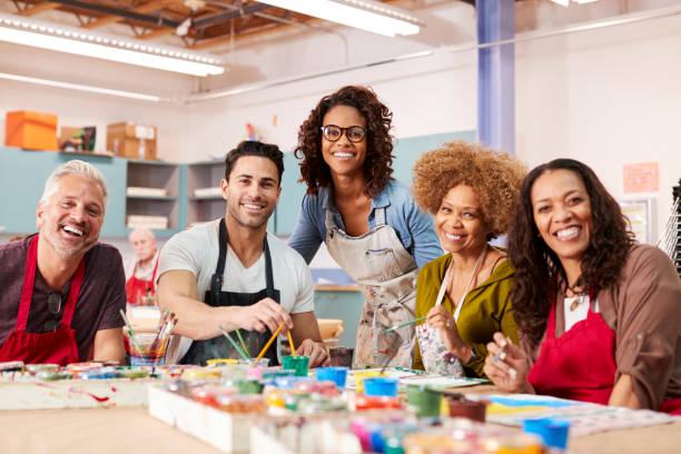 retrato de adultos maduros asistiendo a clase de arte en el centro comunitario con el maestro - clase de arte fotografías e imágenes de stock