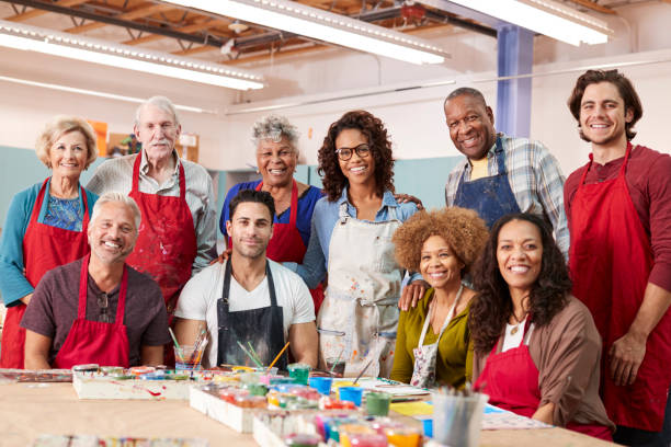 Portrait Of Mature Adults Attending Art Class In Community Centre With Teacher Portrait Of Mature Adults Attending Art Class In Community Centre With Teacher community center stock pictures, royalty-free photos & images
