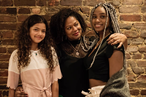 Portrait of mature African-American mother with daughters Portrait of mature mother with beautiful daughters. They are from African-American ethnicity, one is a preteen, the other a young adult. They are looking at the camera with a smile in front of a brick wall. Horizontal indoors waist up shot. haitian ethnicity stock pictures, royalty-free photos & images