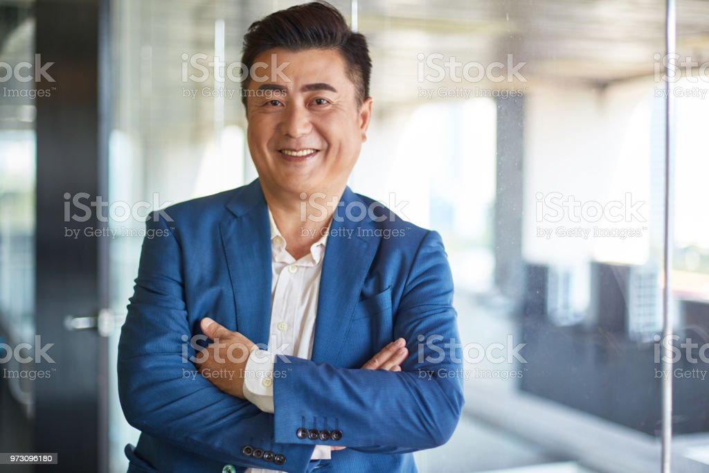 Portrait of mature asian businessman smiling to camera stock photo