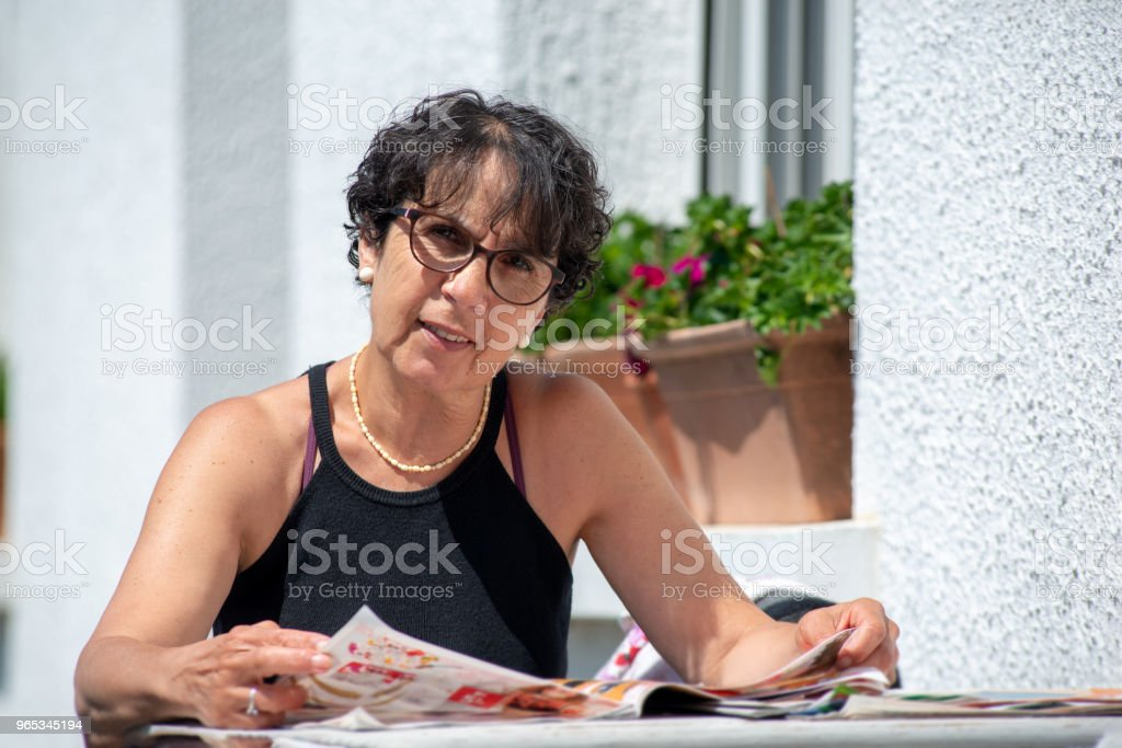 portrait of mature brunette  woman reading magazine in the garden royalty-free stock photo