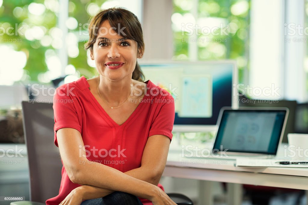 Portrait of mature business woman manager in her desk stock photo