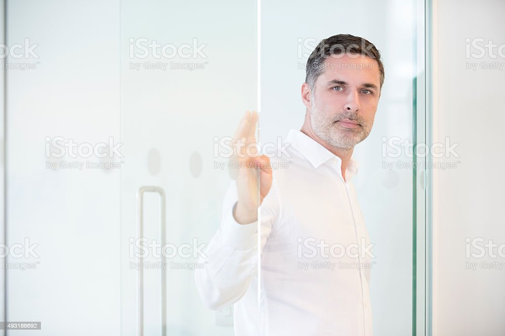 Portrait of mature businessman at the door of his office stock photo