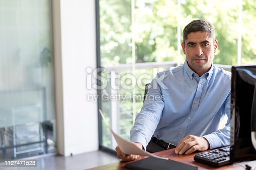 530281723istockphoto Portrait of mature businessman sitting at desk 1127471523