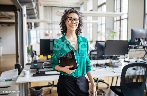 Portrait of mature businesswoman in casuals standing at her desk with digital tablet. Woman entrepreneur in office looking at camera and smiling.