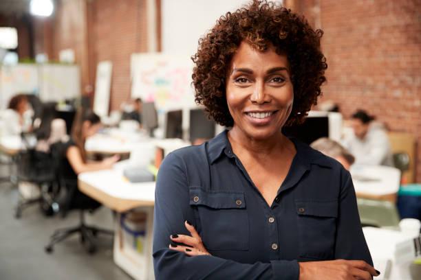 成熟女商人的肖像在開放計畫辦公室與業務團隊工作的背景下 - 女性 個照片及圖片檔