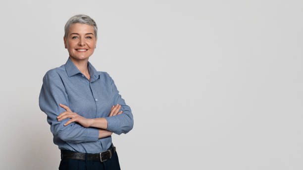 Portrait Of Mature Businesswoman Posing With Folded Arms Over Light Background stock photo