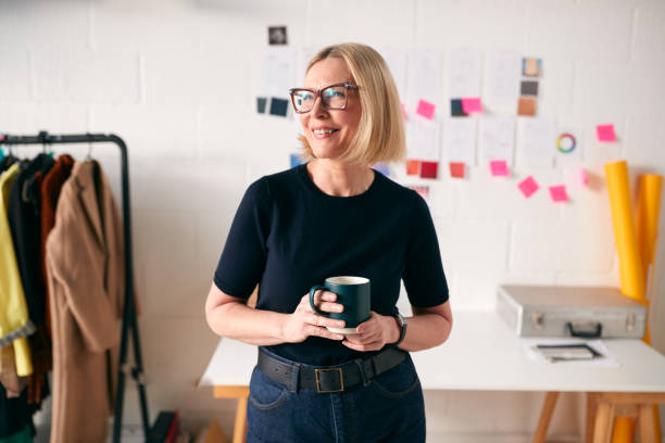 Portrait Of Mature Businesswoman Standing In Front Of Designs And Desk In Start Up Fashion Business stock photo