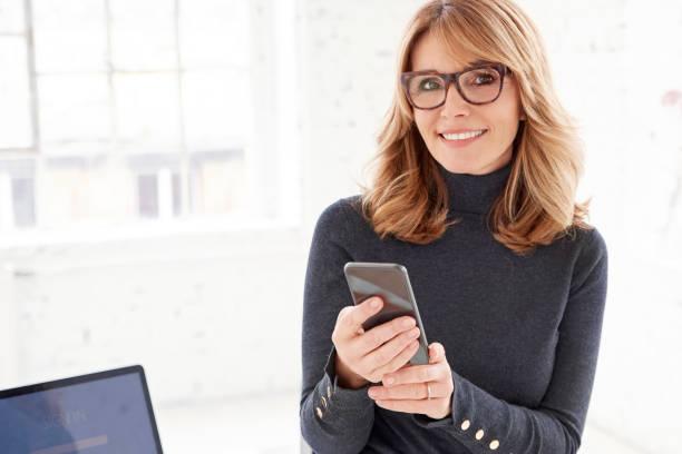 Porträt von Reife Geschäftsfrau SMS beim Sitzen im Büro und arbeiten – Foto