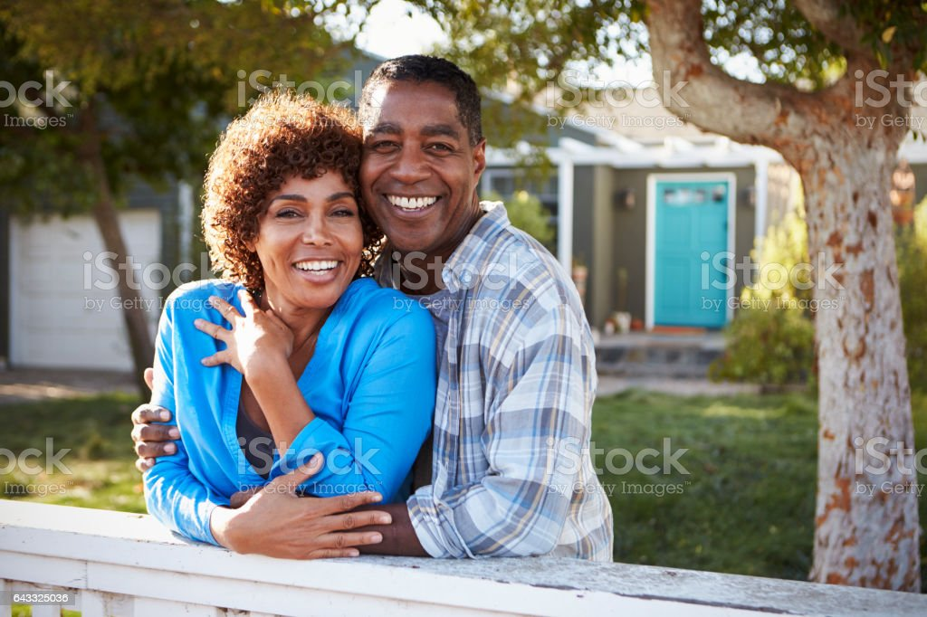 Portrait Of Mature Couple Looking Over Back Yard Fence stock photo