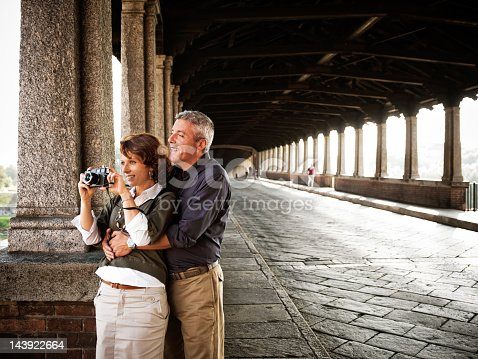 Portrait Of Mature Woman Taking Picture From Camera And Mature Man Hugging From Behind. The covered bridge know as
