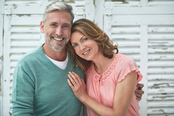 portrait of mature couple smiling outdoors - mão no peito imagens e fotografias de stock