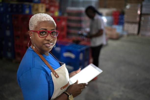 portret van een volwassen werknemer met behulp van digitale tablet in magazijn - warehouse worker stockfoto's en -beelden