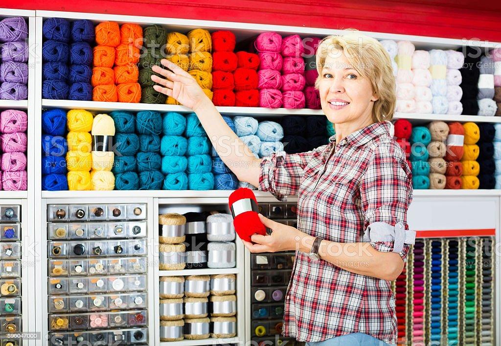 portrait of mature female customer standing next to shelf royalty-free stock photo