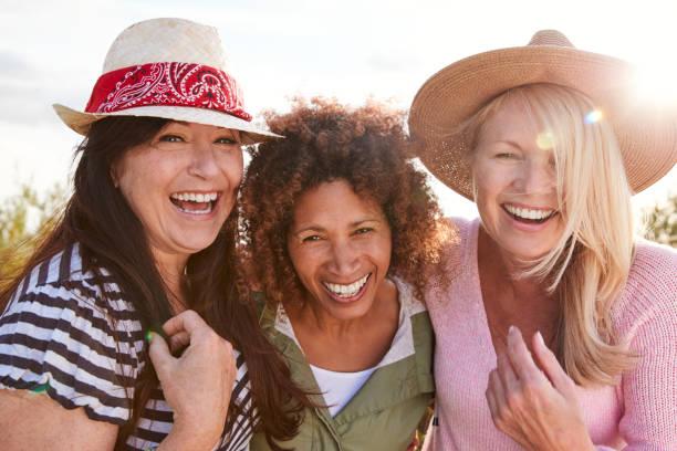 porträt von reifen weiblichen freunden, die im campingurlaub durch das feld laufen - freundin stock-fotos und bilder