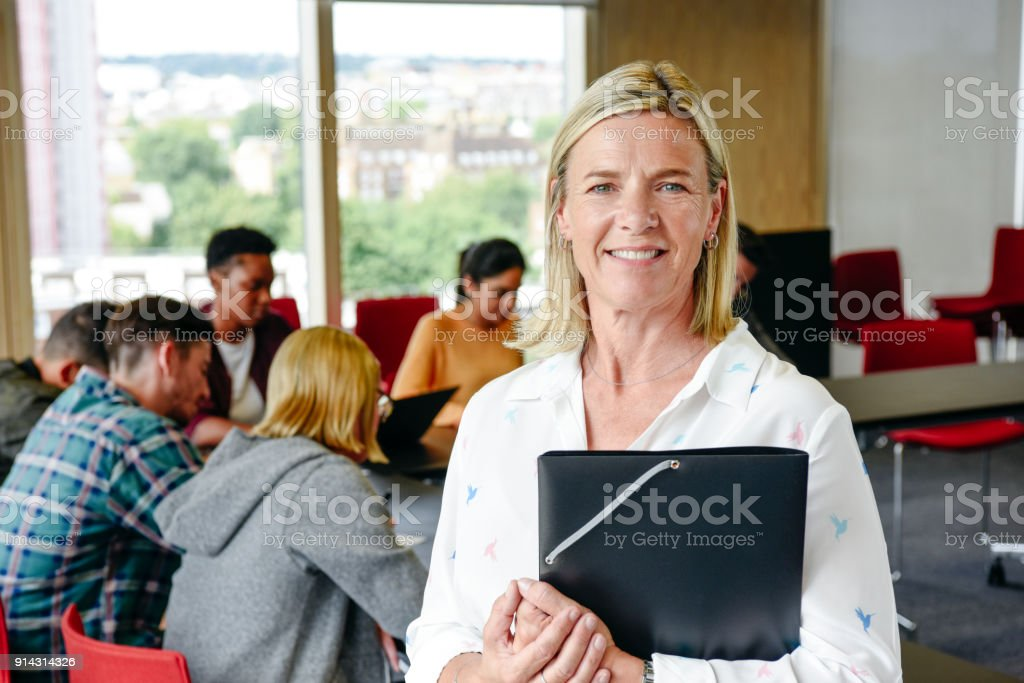 Portrait of mature female lecturer holding folder in classroom, smiling stock photo