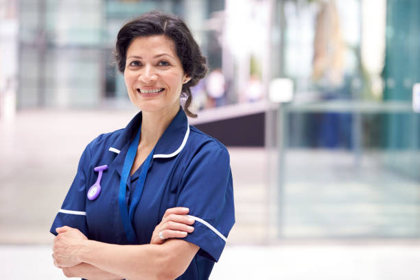 Portrait Of Mature Female Nurse Wearing Uniform Standing In Modern Hospital Building stock photo