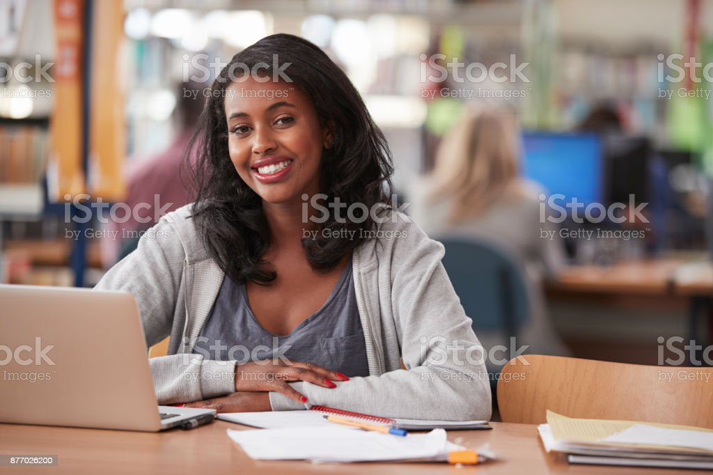 Portrait Of Mature Female Student Using Laptop In Library stock photo