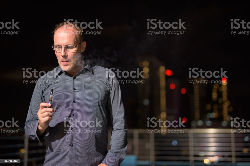 Portrait of mature handsome man smoking electronic cigarette on the rooftop swimming pool stock photo