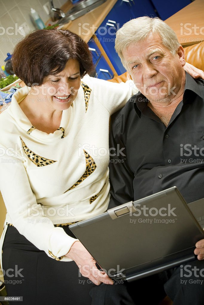 Portrait of mature happy couple with laptop at home royalty-free stock photo