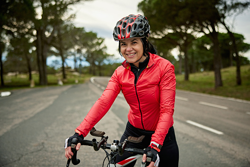 Partial front view of early 50s sportswoman in cycling apparel and helmet pausing at side of Cap De Creus peninsula road and smiling at camera.