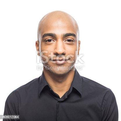 Portrait of mature hispanic man standing against white background