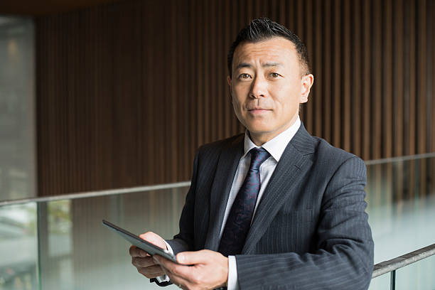 Portrait of mature Japanese businessman with tablet ストックフォト