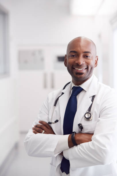 Portrait Of Mature Male Doctor Wearing White Coat Standing In Hospital Corridor stock photo
