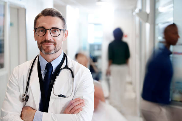 Porträt der Mature Male Doctor Wearing White Coat mit Stethoskop In Busy Hospital Corridor – Foto