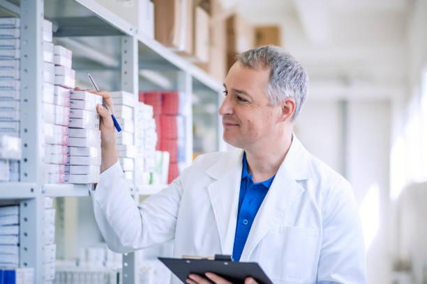 현대 약국에서 일 하는 성숙한 남성 약사의 초상화 - 저장고 제작물 뉴스 사진 이미지