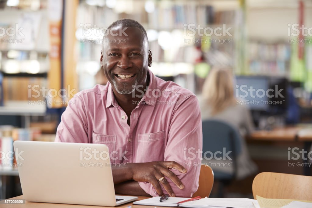 Portrait Of Mature Male Student Using Laptop In Library stock photo