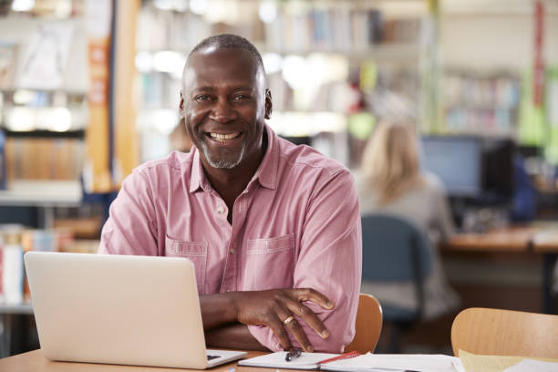 portrait of mature male student using laptop in library - formazione degli adulti foto e immagini stock
