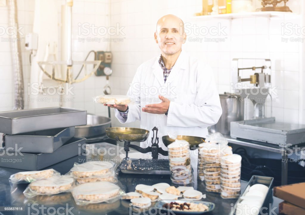 Portrait of  mature male with packing of turron in food factory stock photo