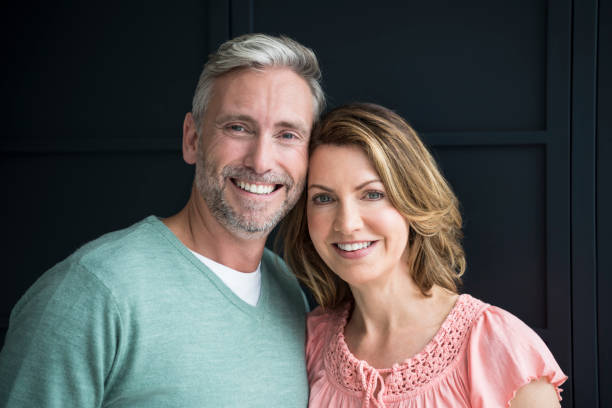 portrait of mature man and woman smiling towards camera with heads touching - couple portrait caucasian foto e immagini stock