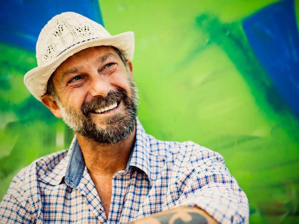 porträt von reifer mann, graffiti auf hintergrund - alte tattoos stock-fotos und bilder