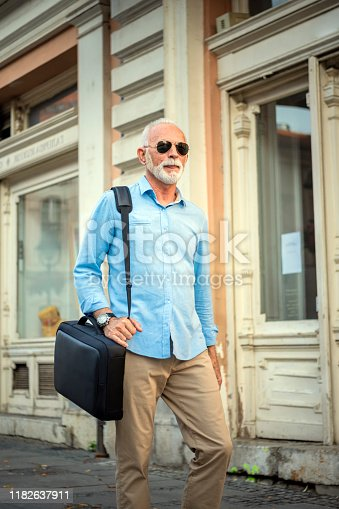636248376istockphoto Portrait of Mature Man in Business Suit in the City Center 1182637911