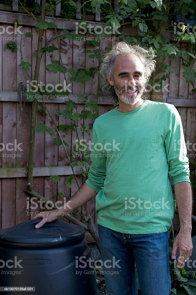 Portrait of mature man standing next to barrel in garden royalty-free stock photo