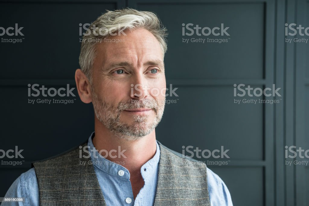 Portrait of mature man with beard and grey hair looking away stock photo