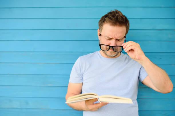 Retrato de hombre maduro con gran negro gafas tratando de leer el libro pero tiene dificultades viendo texto debido a problemas de visión - foto de stock